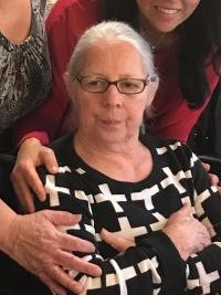 Photo of Virginia Villa, an elderly Latina. She has white hair and is wearing glasses and a black and white sweater. Off to the sides of the picture, two people have their arms around her shoulders.