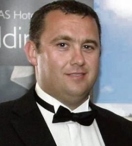 Photo of Jason Corbett, a young man wearing a tuxedo with a bow tie. He has fair skin, dark brown hair, and a receding hairline.