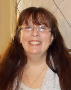 Photo of Donita Elliott, a middle-aged woman with fair skin and very long dark-brown hair, wearing glasses, a white sweater, and a gold necklace. She is smiling broadly at the camera.