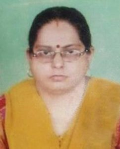 Photo of Swarna Kapoor. She has dark brown hair and fair skin, and is wearing yellow and red. She is wearing glasses and has a dark-red bindi on her forehead.