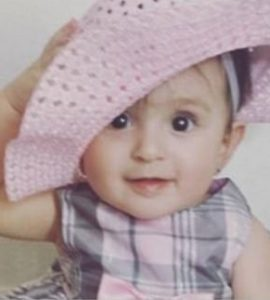 Photo of Sophia Mahaffey, a baby girl wearing a pink and gray checked dress and floppy pink hat. She is holding the hat on her head with one hand. Her wispy dark brown hair is short. She has fair skin.