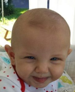 Photo of Faith Wilson, a baby with fair skin and a little bit of dark hair. She is sticking the tip of her tongue out.