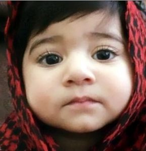 Photo of Inaya Ahmed. She is a toddler girl with light skin and dark brown hair and eyes. She is wearing a red and black checked headscarf.