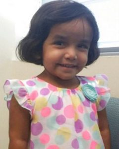 Photo of Sherin Mathews, a young girl with tan skin and chin-length brown hair, wearing a dress with pink polka-dots on it.