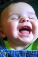 Photo of L'Naya White, a baby with her mouth open in laughter. She has fair skin. She is wearing a green and blue top.