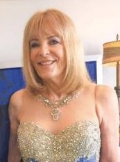 Photo of Maureen Boyce, a middle-aged woman with fair skin and straight blonde chin-length hair. She is wearing a fancy sequined dress and silver necklace.