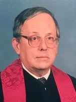 Photo of an elderly man wearing glasses and Methodist religious vestments.