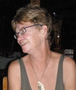 Photo of Patricia Kearney, a woman with tanned skin and short dark-blonde hair. She is wearing glasses and a tank top. She is looking off to the left of the photo.
