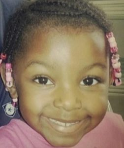 Photo of Sanaa Cunningham, a small African-American girl with a broad smile, tan skin, and hair in tiny braids decorated with pink beads.