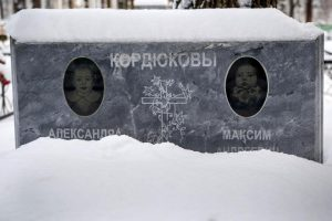 Gravestone of Sasha and Maxim Kordyukova. Their names are written in Cyrillic characters, and above each name is a dim black-and-white image of a young child. The bottom of the photograph is torn off so that the dates of birth and death cannot be seen.