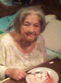 Photo of Beverly Nickerson, an elderly woman with gray hair and pale skin, wearing a nightshirt and sitting on the edge of a bed, eating from a plate on a bedside table. The photo has caught her in the middle of licking her lips.