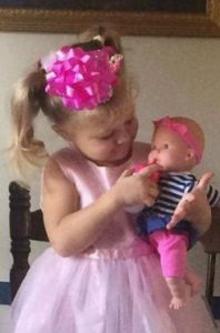 Photo of Mariah Woods, a toddler girl with fair skin and blonde hair in two ponytails. She is wearing a pink formal dress and has a big pink gift ribbon glued to her hair; she is pretending to feed a baby doll.