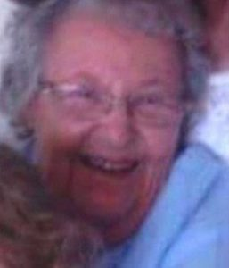 Photo of Betty Guy, an elderly woman with light skin and light-gray hair, wearing glasses and a blue top. She is smiling and hugging someone off-camera.