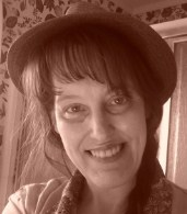 Sepia-tone photo of Ellen MacKenzie, a middle-aged woman with light skin and dark hair, wearing a hat and smiling.