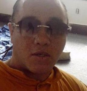 Photo of Murray Upshaw, a man with light skin, wearing sunglasses and an orange shirt. He is balding and little of his dark hair is visible.