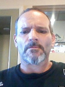 Photo of Michael Jones, a middle-aged man with light skin and brown eyes. He is balding and has a salt-and-pepper mustache and beard.