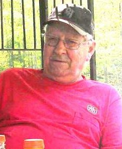 Photo of Douglas Fischer, an elderly man, somewhat chubby, wearing a baseball cap and T-shirt and leaning back against a metal fence, looking contemplatively into the middle distance through wire-rimmed glasses.
