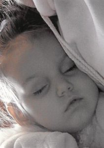 Photo of a sleeping fair-skinned toddler girl, draped in cloth.