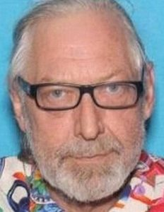 Photo of Ronald Bettig, an elderly man with pale skin and white hair and beard, wearing glasses and a colorful shirt.