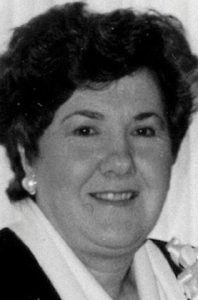 Black-and-white photo of Irene Carter, a woman with fair skin and dark curly hair, wearing pearl earrings.
