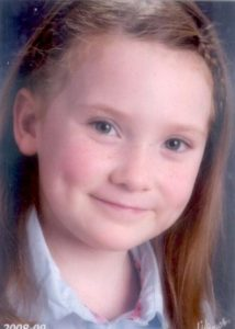 Photo of Camden Fry, a young girl with light-brown hair, blue eyes, and pale skin. Her hair is held back in a hair band and she is smiling for the camera, revealing dimples in her cheeks.