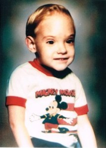 Photo of Stephen Hughes, a small boy with a large head, wearing a Mickey Mouse T-shirt.