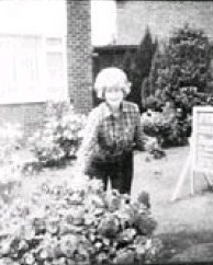 Blurry black and white photo of Lorna McCaddon, a light-skinned woman with a beehive hairdo, wearing jeans and a flannel shirt, photographed outside in a garden.