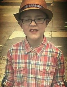 Photo of Ethan Okula, a small boy with fair skin. He is wearing a straw trilby, dark-rimmed glasses, and a flannel shirt.