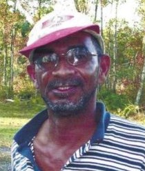 Photo of Dwight Ridley, a man with dark-brown skin and a salt-and-pepper beard, wearing a baseball cap and polo shirt, photographed outdoors.