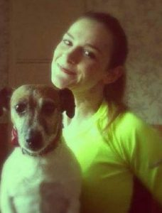 Photo of Natasha Wild, a young woman with light-brown hair and pale skin, wearing a yellow shirt. She is photographed with a brown-and-white, medium-sized dog.