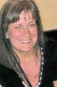 Photo of Sharon Birchwood, a woman with fairskin and straight, shoulder-length gray hair.