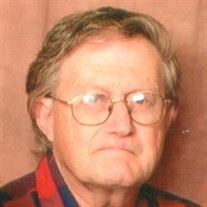Photo of Bruce Clayton, a middle-aged man with thinning light-brown hair and fair skin, wearing glasses. He is wearing a flannel shirt, and frowning at the camera.