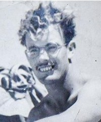 Black and white photo of Kenneth Coombes, a young man with curly hair, glasses, and fair skin.