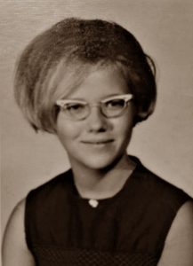 Sepia portrait photo of Sharon McCleary as a young woman. She has fair skin and hair cut in a bob; she is wearing old-fashioned glasses and a black sleeveless top.