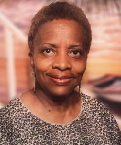 Photo of Bertha McGill, a middle-aged African-American woman with her hair cut quite short. She is wearing a leopard-print shirt and dangle earrings.
