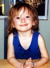 Photo of Eliza Jane Scovill, a toddler with tangled auburn hair, fair skin, and brown eyes wearing a blue dress. She is smiling for the camera.