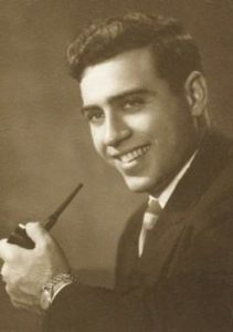 Antique sepia portrait photo of Gerald Sohn, a young man with dark curly hair and light skin, wearing a suit and tie and holding a pipe.