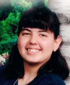 Photo of Courtney Turney, a young woman with dark-brown hair and tan skin. She is smiling for the camera.