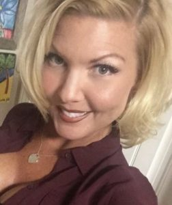 Selfie-style photo of Kathleen West, a woman with fair, slightly tanned and freckled skin and blonde hair. She is wearing a maroon blouse left open to show a little cleavage, and a heart-shaped gold necklace.