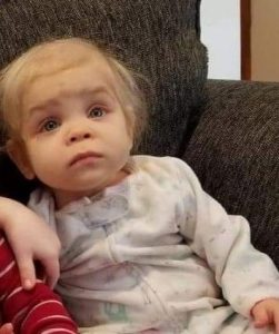 Photo of a baby with pale skin and wispy, light-blonde hair, wearing pajamas with a zipper up the front. She has a puzzled, slightly worried expression on her face.