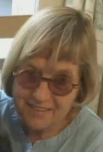 Photo of Ann DeLucia, an elderly woman with pale skin and chin-length white hair, wearing a pair of round sunglasses.