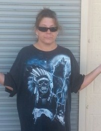 "Photo of Dawn Liebig, a middle-aged woman with tanned skin and brown hair in a messy ponytail. She is wearing sunglasses and a T-shirt printed with a skeleton in a feathered war bonnet and a wolf howling at the moon. She has her hands upturned in an ""I don't know"" gesture."