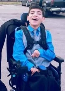 Photo of a teenage boy in a power chair, wearing a blue shirt and tie. He is smiling broadly. His dark hair is cut short.