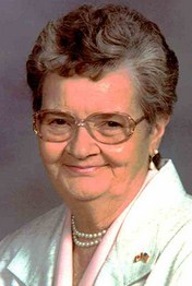Portrait photo of Evelyn Bailey, an elderly woman wearing a white suit jacket and a string of pearls. Her salt-and-pepper hair is permed and cut short. She has pale skin and is wearing large glasses and a flag lapel pin. She is smiling for the camera.
