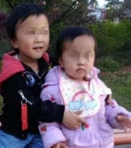 Photo of two Chinese toddlers, a boy in a black and red coat, and a girl in a purple coat. The boy has his arms around the girl. Their eyes are pixelated to keep them anonymous.