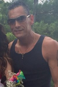 Photo of Mark Randolph. He is a middle-aged, muscular man wearing a black tank top. His tanned skin is decorated with tattoos. He is wearing sunglasses, and his salt-and-pepper hair is cut short. He is smiling slightly.