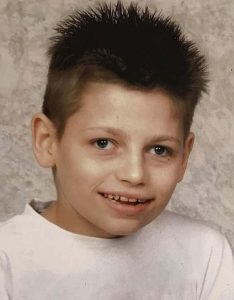 School photo of a boy with brown spiky hair, wearing a white T-shirt.