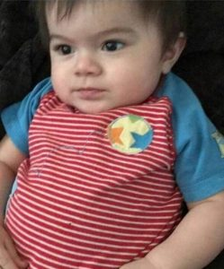 Photo of a baby boy wearing a striped shirt. He has dark brown eyes and wispy brown hair.