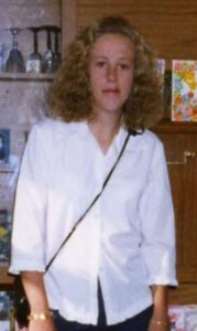 Photo of a young woman with curly blonde hair, wearing a white blouse.