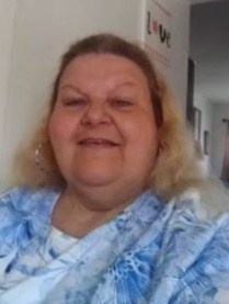 Photo of Debbie Lynch, a middle-aged, heavyset woman with blonde hair and thin eyebrows, smiling for the camera.